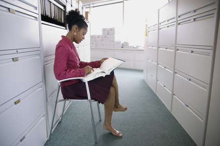 Side profile of a businesswoman sitting on a chair reading a file Stock Photo - 16043882
