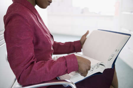 Businesswoman sitting holding a file Stock Photo - 16043883