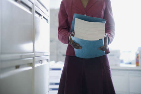 View of the torso of a businesswoman carrying documents