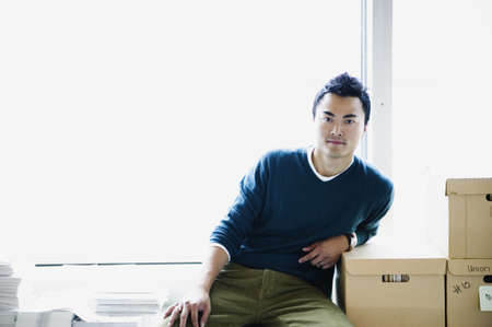 way of behaving: Portrait of a young man sitting leaning on cardboard boxes