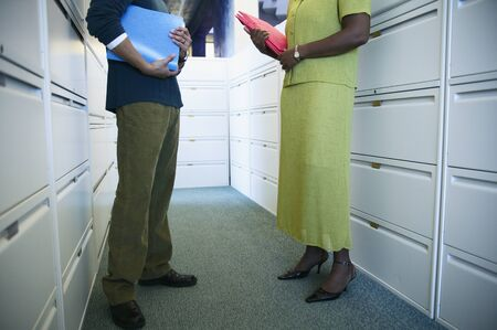 way of behaving: Low section view of a young businessman and a young businesswoman standing holding files LANG_EVOIMAGES