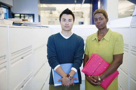 way of behaving: Portrait of a young businessman and a young businesswoman standing together in an office holding files