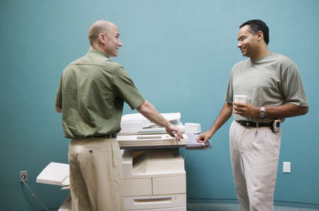 Two businessmen standing at a photocopying machine Stock Photo - 16043912