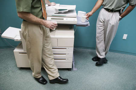 low section view: Low section view of two businessmen standing at a photocopying machine