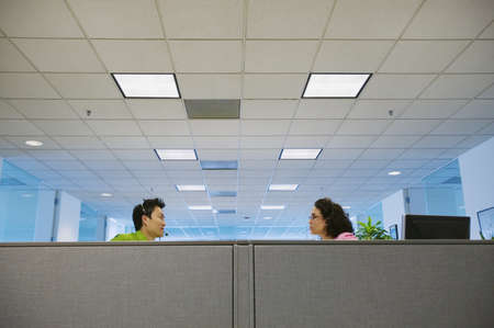 only 2 people: Young businesswoman and businessman talking to each other in an office