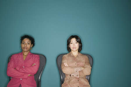 way of behaving: Portrait of two young businesswomen sitting on chairs with their arms folded