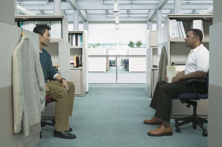 Businessmen sitting on chairs opposite from each other in an office LANG_EVOIMAGES