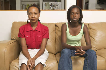 teenaged: Portrait of mid adult woman with her teenage daughter sitting on a couch