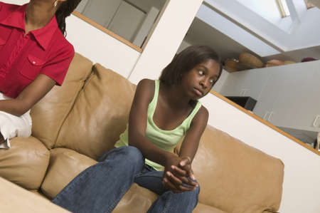 Low angle view of a mid adult woman and her teenage daughter sitting on a couch Stock Photo - 16043951
