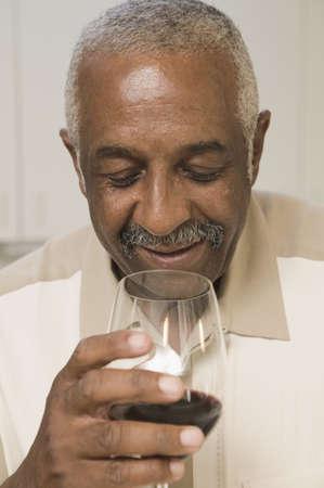 mid adult man: Hombre de mediana edad que mira en un vaso de vino tinto