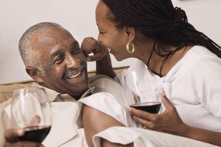 mid adult couple: Pareja de mediana edad sentado en conjunto, poseen vasos de vino tinto LANG_EVOIMAGES