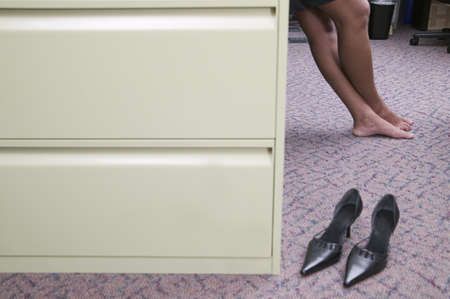 Low section view of mid adult woman leaning and a pair of shoes besides a filing cabinet Stock Photo - 16043953