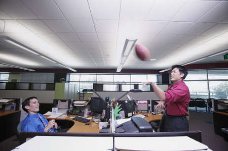 annexation: Two businessmen playing with a football in the office