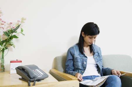 Young woman sitting on a couch reading a magazine waiting in a waiting room Stock Photo - 16044023