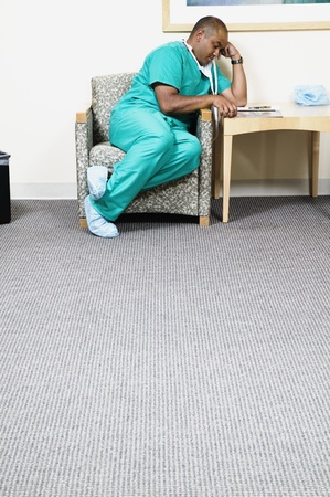 Male doctor sitting in a chair reading a magazine