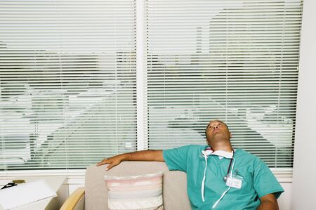 Male doctor sitting on a chair wearing scrubs