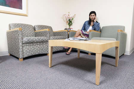 davenport: Young woman sitting in a waiting room holding a magazine