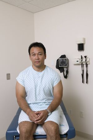Portrait of a male patient sitting on an examination table in a doctors office