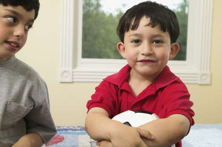 two persons only: Portrait of two boys sitting on a bed