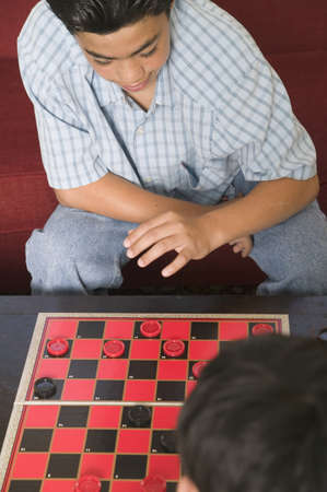 two persons only: High angle view of two young boys playing checkers