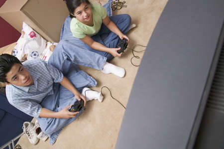 children's wear: High angle view of a young boy and a young girl playing a video game LANG_EVOIMAGES