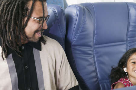 hydroplane: Mid adult man sitting in an airplane looking at a young girl