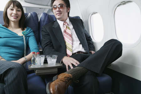 business for the middle: Portrait of an adult couple traveling in an airplane