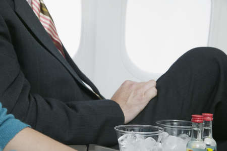 two persons only: Midsection view of businessmen traveling in an airplane LANG_EVOIMAGES