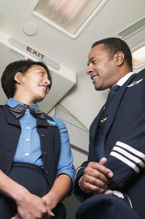 invariable: Low angle view of a male purser and female air hostess looking at each other