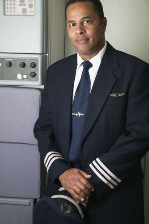 invariable: Portrait of a mid adult male pilot standing holding a cap