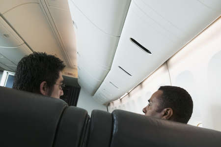 hydroplane: Mid adult men traveling in an airplane LANG_EVOIMAGES