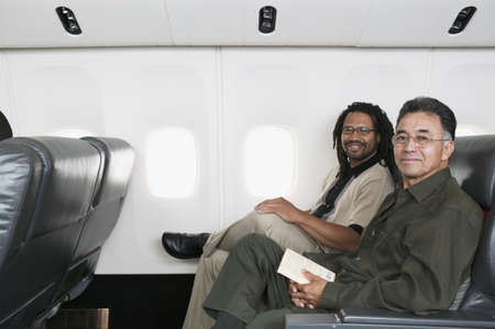 impasse: Portrait of a two mid adult men traveling in an airplane smiling LANG_EVOIMAGES