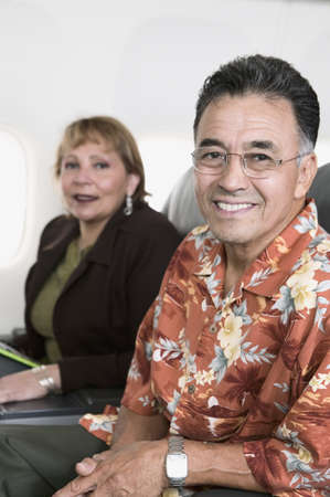 mid adult couple: Portrait of a mid adult couple traveling in an airplane