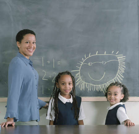 credence: Young female teacher standing with two young girls near a blackboard