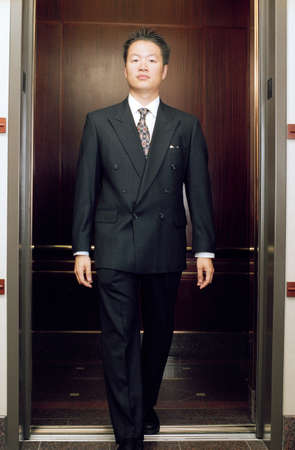 way of behaving: Young businessman stepping out of an elevator