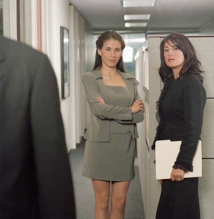 joyousness: Two young businesswomen standing in an office looking at a young businessman