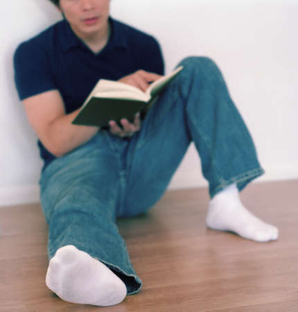 restfulness: Young man sitting on a floor reading a book LANG_EVOIMAGES