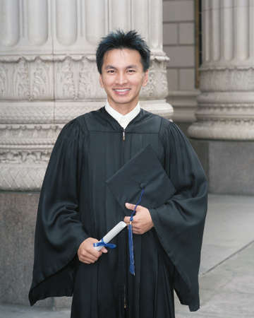 Young male graduate holding a degree Stock Photo - 16044185