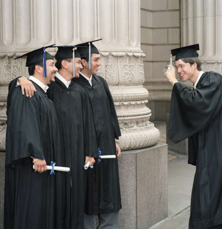 alumnae: Young male graduate photographing three male graduates
