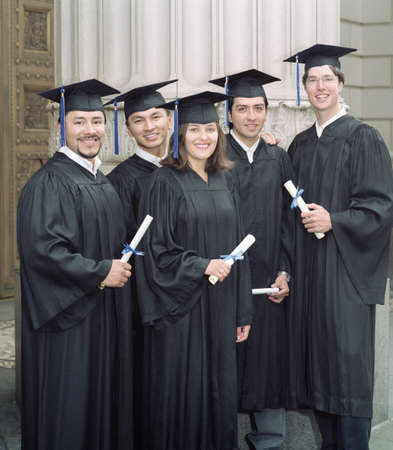 alumni: Group of young graduates standing holding degrees