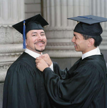 Young male graduate adjusting his friends collar