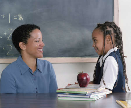 Young girl standing talking to a young female teacher in\ class