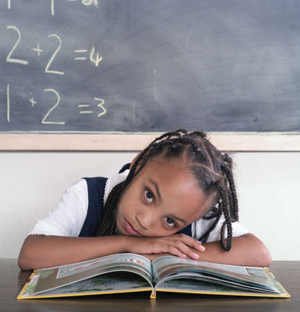 Young girl with her head down on a table in class