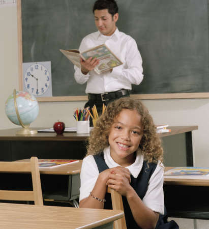 Young female student and a young male teacher in a classroom