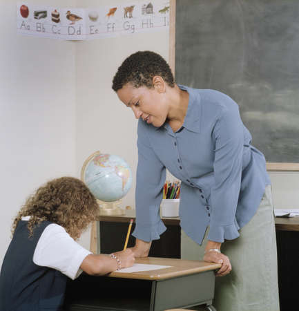 groping: Young female teacher watching a young girl write LANG_EVOIMAGES