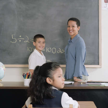 Young female teacher and a young boy standing in front of a black board Stock Photo - 16044202