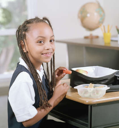 Young girl eating food at lunch break