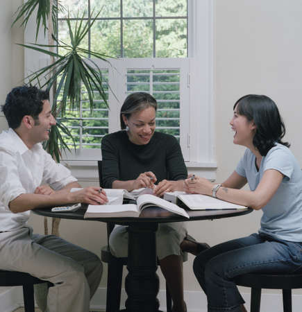Three young people sitting at a table studying Stock Photo - 16044205