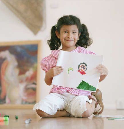 Young girl sitting on the floor holding up a drawing Stock Photo - 16044206