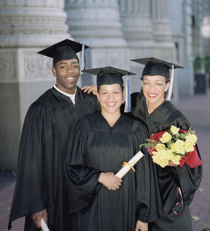 three persons only: Three young graduates standing outdoors looking at camera LANG_EVOIMAGES
